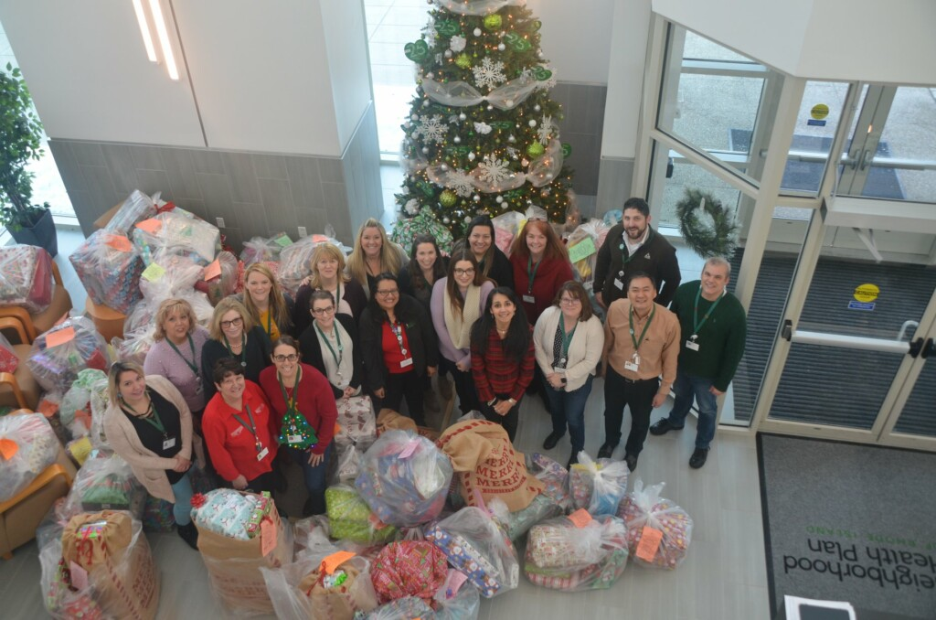 Employees posing with donated christmas gifts
